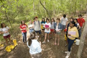 Professor David Bill's biology lab class conducts field experiments on a trail at Lake Herrick.