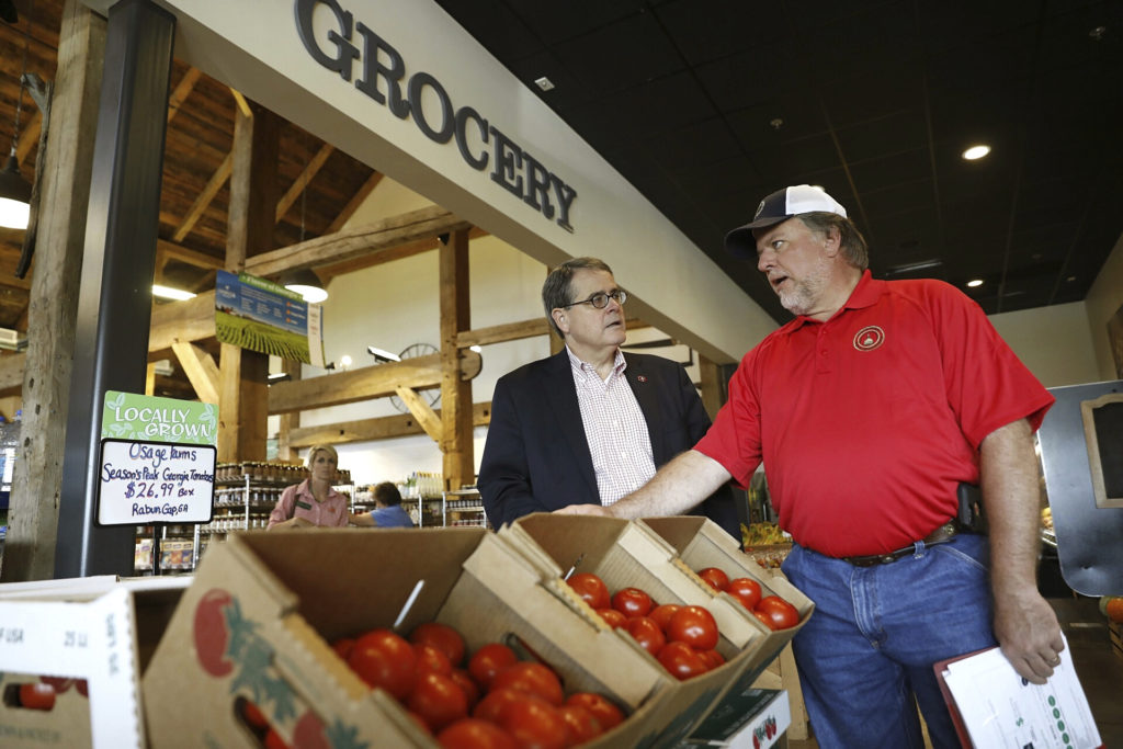 President Jere W. Morehead talks with State Rep. Terry England inside the grocery at the Farmview Market in Madison.