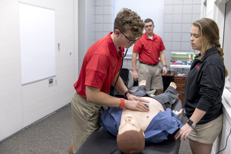Athletic training majors Luke Lammert, left to right, Ryan Bussey, and Katie Plummer check the heartbeat on a SimMan Essential simulated patient during a demo in the new Athletic Training Simulation Lab at the Ramsey Center on Thursday afternoon. (Photo credit: Andrew Davis Tucker)