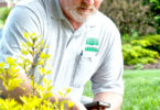 IPM app John Watson with iPhone and shrub 2-v.action