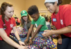 UGA students, from left, Brooke Johnson, Jillian Schmidt and Lindsey Shelton wrap gifts with Desmond Barnes, a student at Winterville Elementary School, during Shop with a Bulldawg. Schmidt is executive director of the student group.