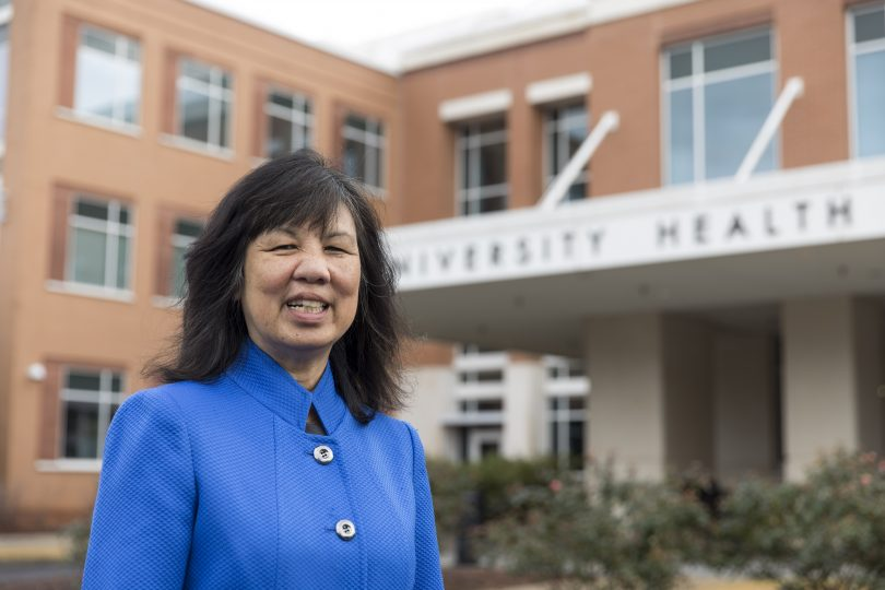 Jean Chin smiles in front of the University Health Center