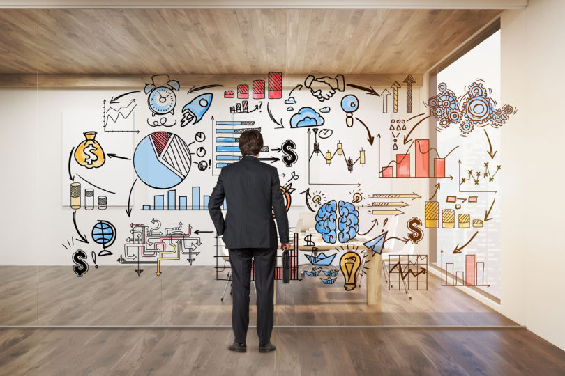 Businessman with suitcase looking at startup icons on glassboard
