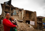 Mother and child outside earthquake ruined home