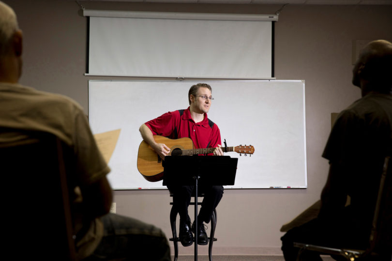 Michael McGough plays guitar and sings with a group of men at Living Hope Church during his lunch break.