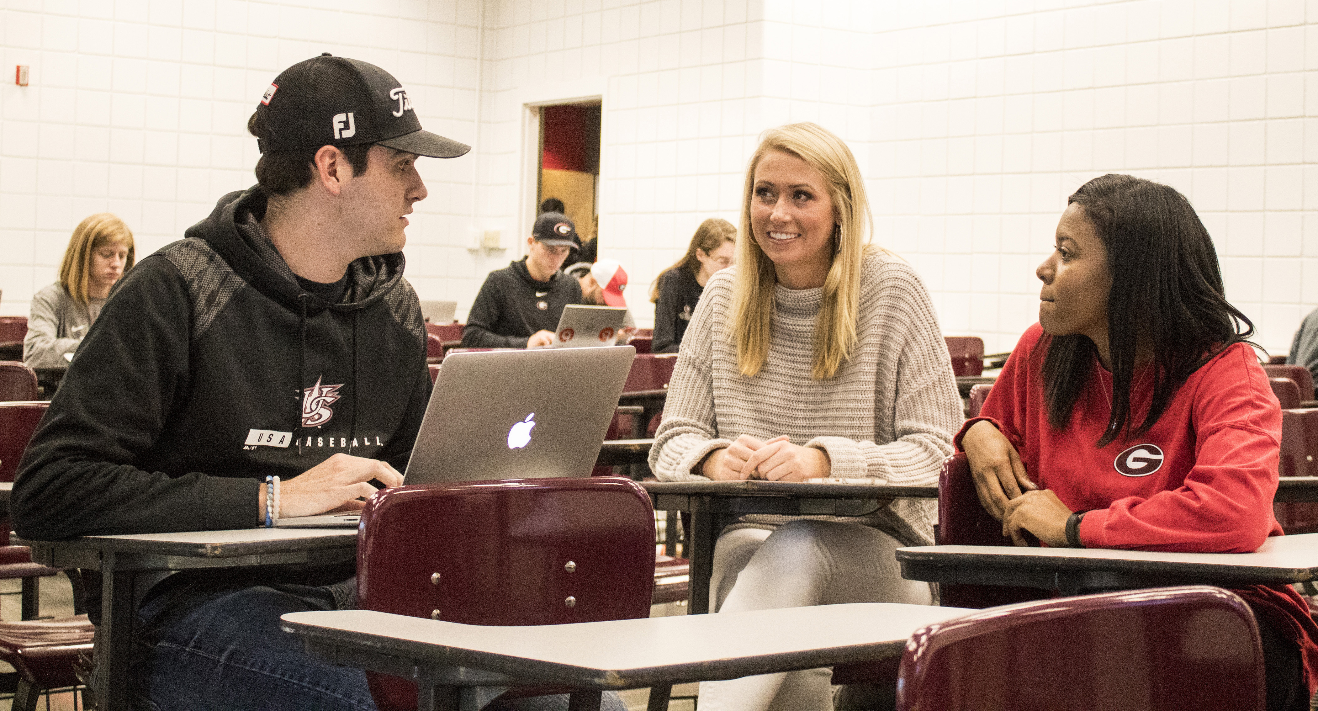 From left, Rusty Gay, Kacey Caudill and Brianna Davis, all sport management  students in the University of Georgia College of Education, talk after a  class ...