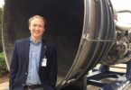 Professor Ben Davis stands in front of a Space Shuttle Main Engine.