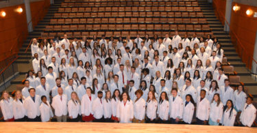 Photo of pharmacy students in white coats.