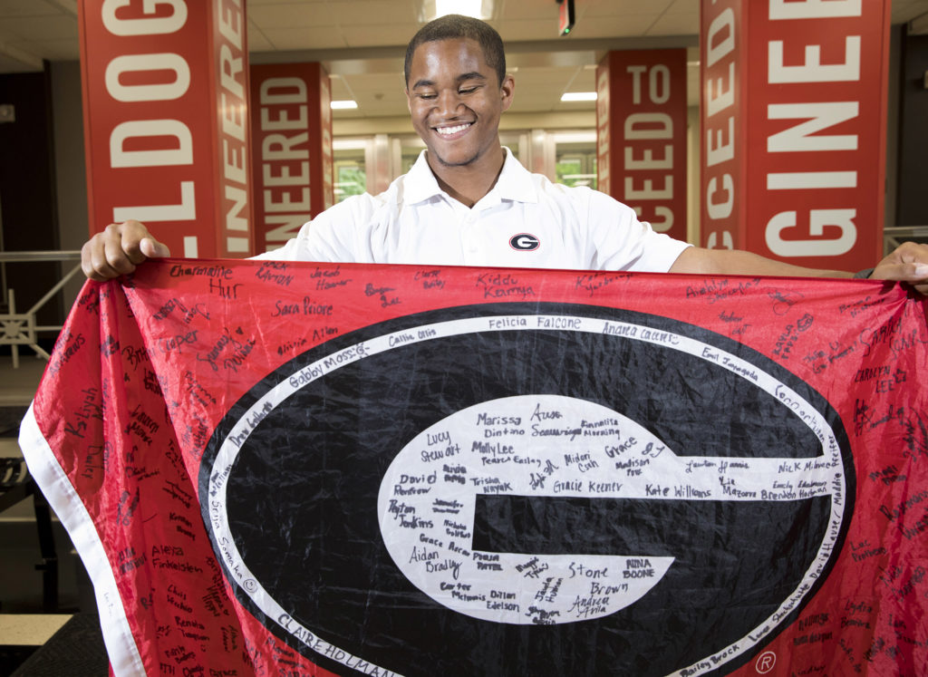 Christopher Johnson holds a red G flag that has signature on it