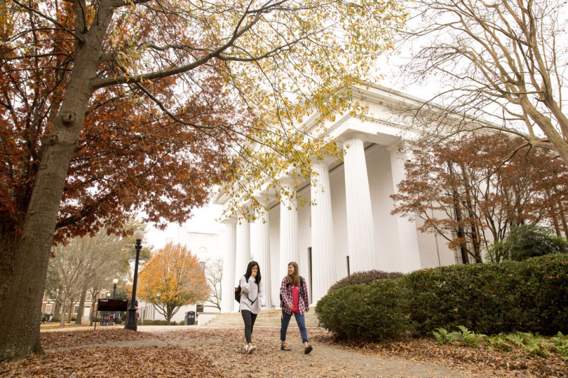 Chapel with fall leaves and students walking in front of it
