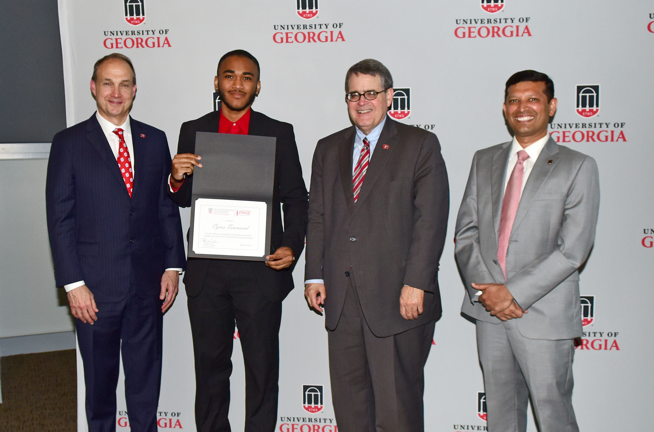 Photo:  Jim Dinkins, Coca-Cola North America president, presents a certificate to Cyrus Townsend, a Coca-Cola First Generation graduate, alongside UGA President Jere W. Morehead and Rahul Shrivastav, UGA vice president for instruction | UGA.edu