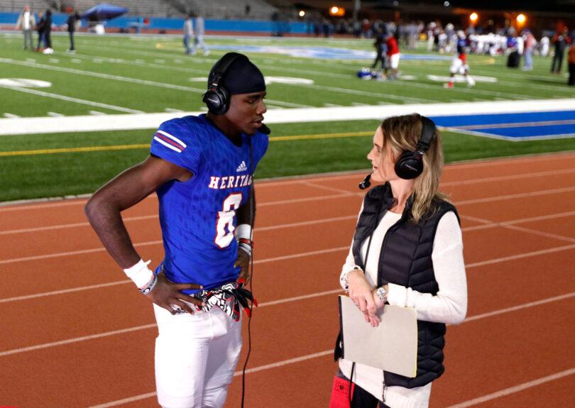 A woman interviews a football player after a football game.