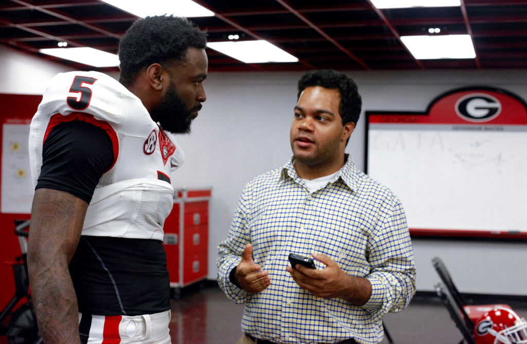 A man interviews a football player in the locker room.