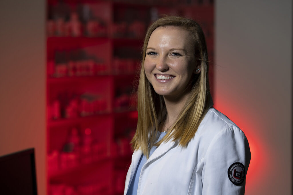 Woman in white pharmacy coat smiling