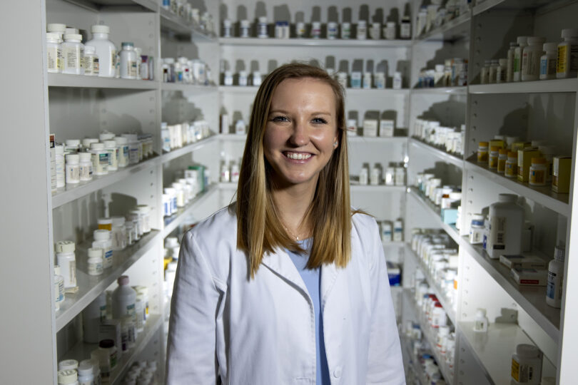 Rebecca Bruning in white pharmacist coat with pharmacy in the background
