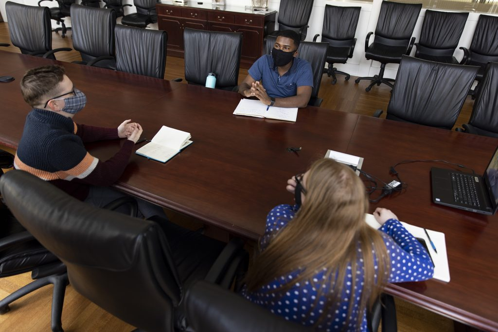 Photo of Ricky Belizaire and two students in a meeting.