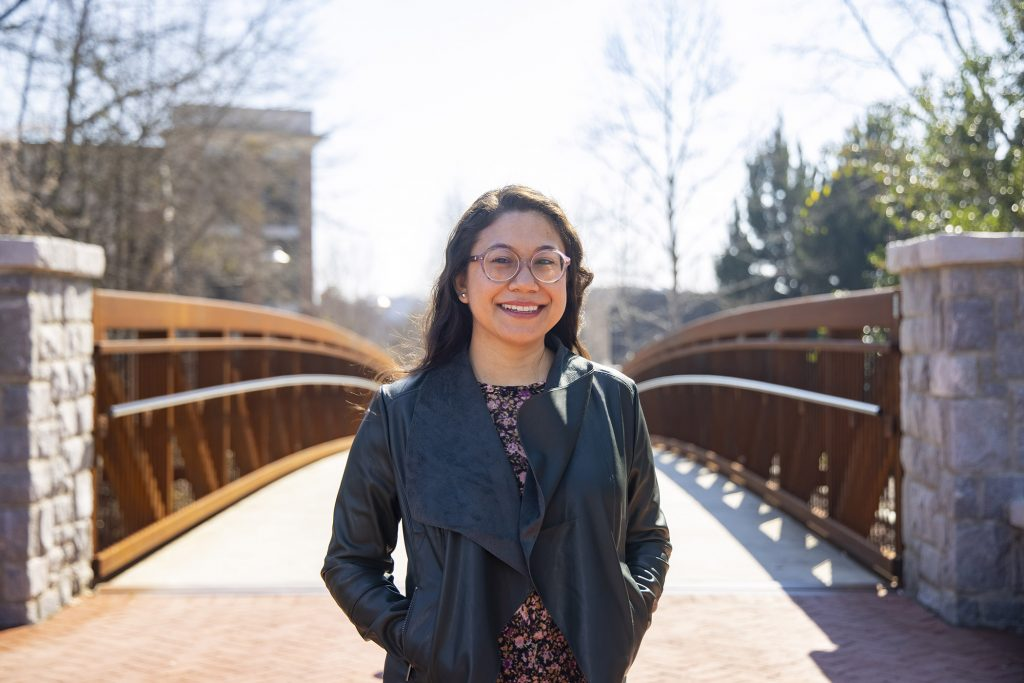 Shannon Perry standing on a bridge on campus.
