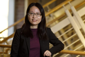 """Donglan """"Stacy"""" Zhang poses in a campus building."""