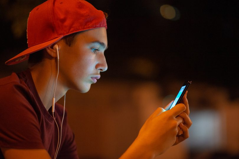 Close-up portrait of a young man with smartphone
