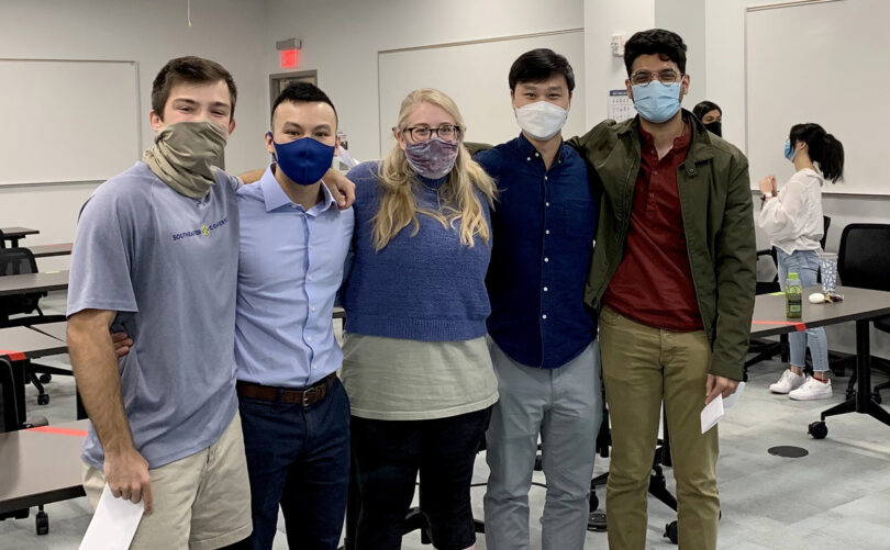A group of five people wearing face coverings for the pandemic