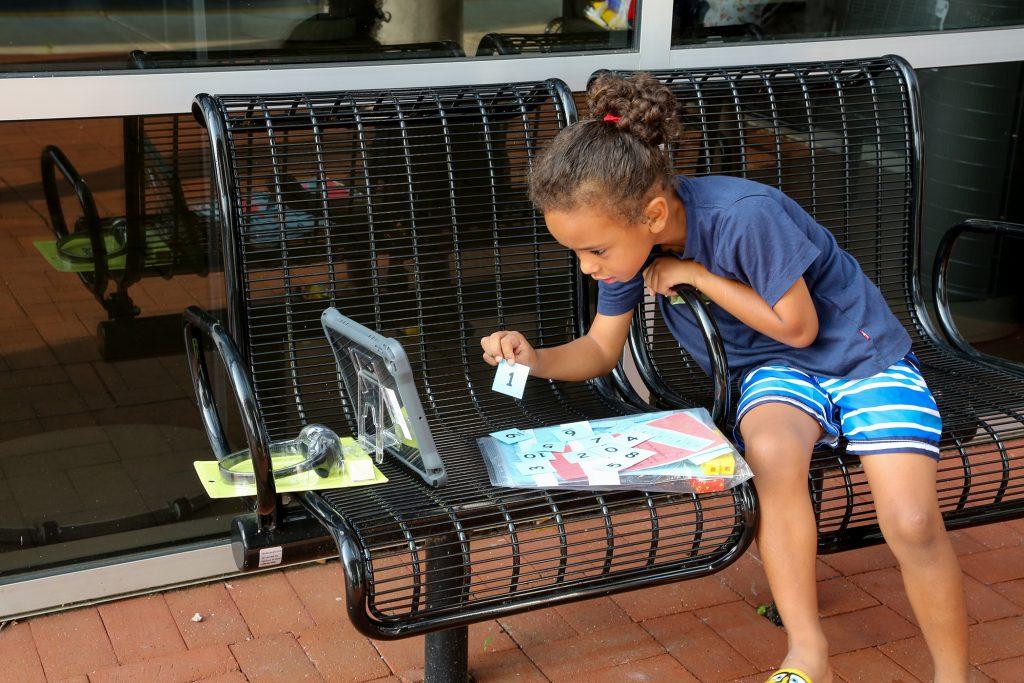 Girl doing virtual homework on a bench outdoors.