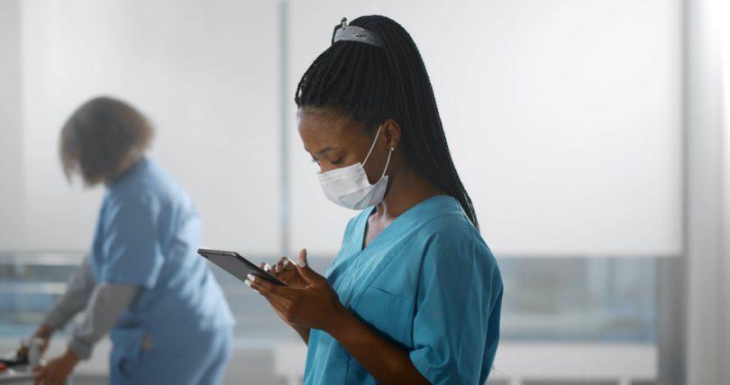 nurse wearing safety mask using digital tablet