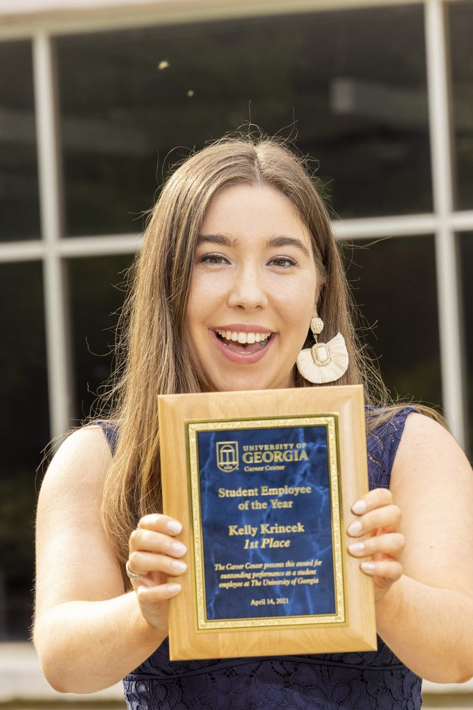 Kelly Krincek holds her Student Employee of the Year plaque
