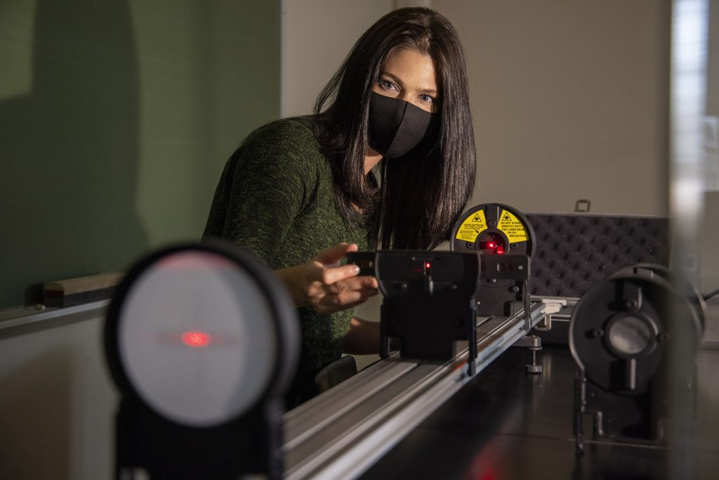 Lauren Sgro sets up a lab demo with a laser.