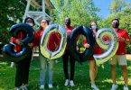 Students hold balloons that read 3,009.