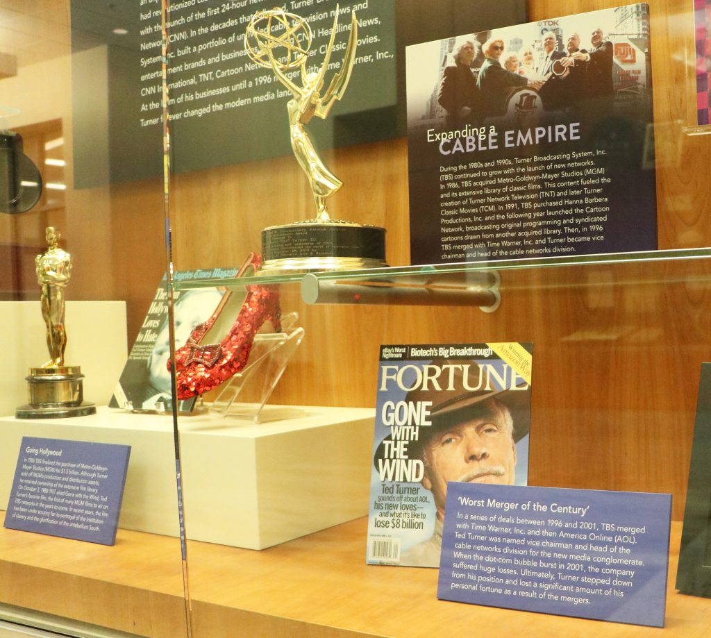 A glass display case with trophies and magazine covers.