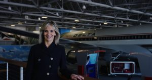 Allison Ausband stands in front of a Delta plane.