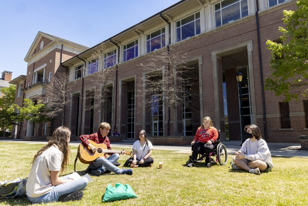 a group of five students sit on a lawn. One student is in a wheelchair. One student plays guitar.