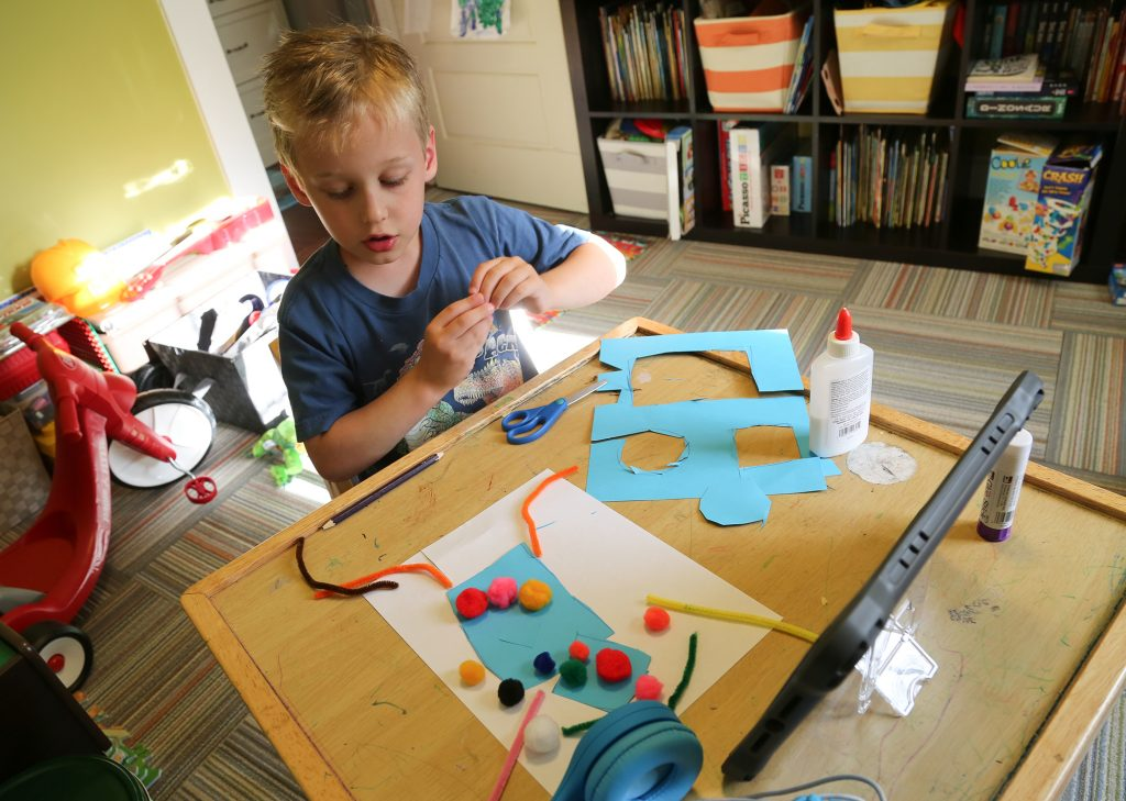 A kindergarten student works on a craft project.