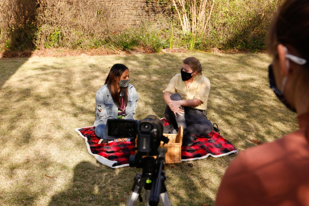 Two students sit on a blanket in front of a camera.
