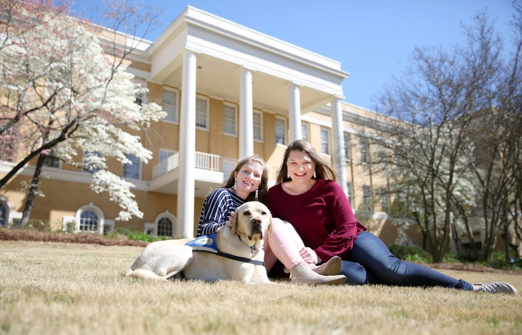 Amelia and Megan Holley with Spencer, Amelia's service dog, in front of Dawson Hall.