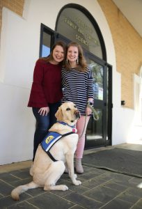 Megan and Amelia Holley pose with a service dog.