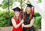 Amelia and Megan Holley wear graduation mortarboards and ring the UGA Chapel Bell.