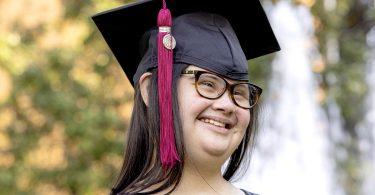 Marina Martinez wears a graduation mortarboard smiles.