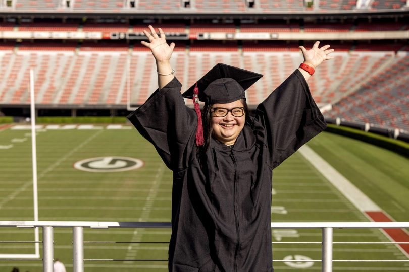 Marina Martinez wears a graduation cap and gown throws her hands up in excitement. Football field in the background.