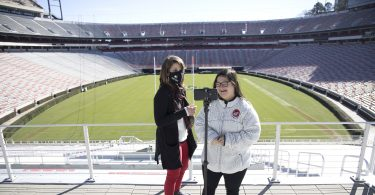 Whitney Ostrander and Marina Martinez stand in front of a football field and film on an iPhone.