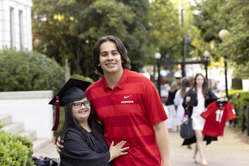 Marina Martinez wears a graduation gown and poses for a photo with her brother in front of UGA's Arch.