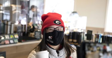 Marina Martinez wearing a COVID mask and winter hat gets coffee.