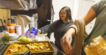 Marina Martinez adds some lettuce to her plate as she makes dinner with her roommates.