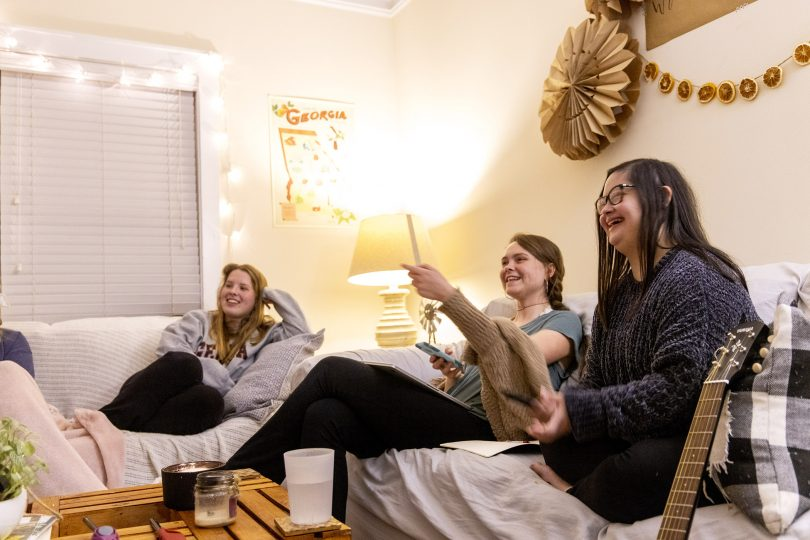 Three women watch TV together in their apartment.
