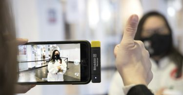 Whitney Ostrander gives a thumbs up sign, Marina Martinez is seen in the screen of an iPhone.