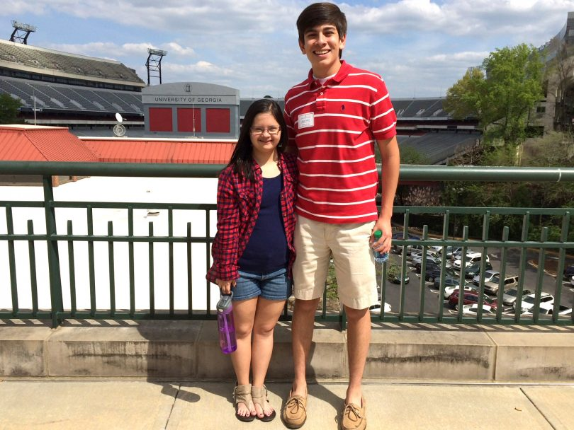 Marina and her brother, Juan Carlos Martinez, pose for a photo in front of Sanford Stadium during Marina's high school years.