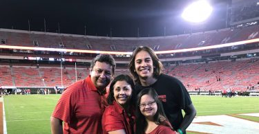 A family of four hugs with the UGA football field in the background.
