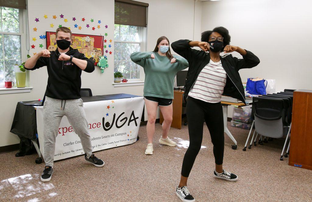 Three UGA students dance with masks on.