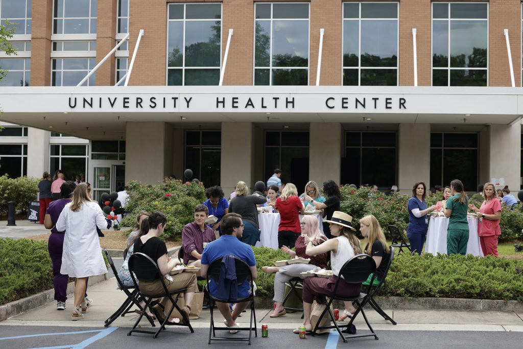 Health Center employees eat lunch at tables outside the center.