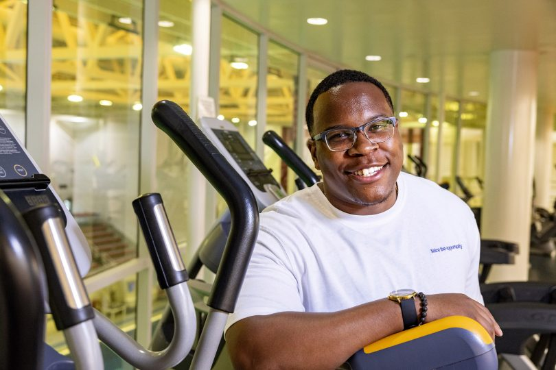 Zerian Hood smiles as he stands in a gym full of exercise equipment
